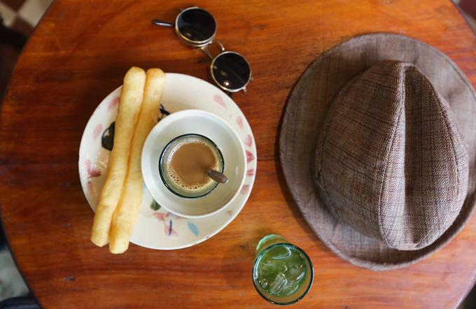 """Quán còn có cả món cà phê chấm quẩy, đồ uống rất quen thuộc với người Sài Gòn cách đây mấy chục năm.  """"Tôi làm trong khu đô thị Thủ Thiêm nên cũng hay ghé đây uống cà phê, ăn trưa. Thành phố có nhiều quán cà phê dạng hoài niệm nhưng tôi ưng nơi này nhất vì không gian rộng và đa dạng đồ cổ. Chủ quán thường mặc áo bà ba, giới thiệu nhiệt tình về từng món đồ, kỷ vật, cách bài trí... giúp tôi có thêm vốn hiểu biết về Sài Gòn, hòn ngọc Viễn Đông"""", anh Thành Tài (30 tuổi, quận 2) chia sẻ."""