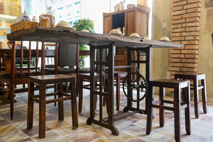 """ó những chiếc bàn được thiết kế từ bộ khung của máy may của hãng Singer, nổi tiếng khắp miền Nam một thời. """"Từ nhỏ tôi ở với ông bà nội, họ làm nghề may quần áo nên những vật dụng này là một phần tuổi thơ của tôi được tái hiện trong quán"""", anh Hiệp chia sẻ."""