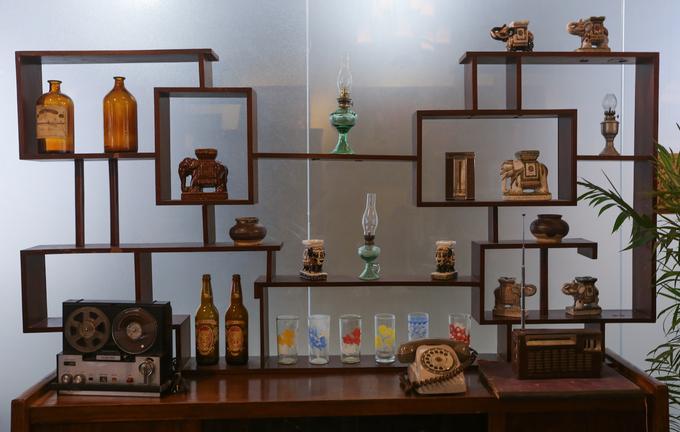 Cách bài trí đồ đạc trong phòng khách ngày xưa với điện thoại bàn, đài cassette, đèn dầu, bình rượu... được tái hiện lại trong quán.