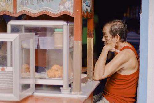 Ông Há - chủ quán, ngồi bên chiếc xe hủ tiếu đã gắn bó suốt 38 năm. Ảnh: Linh Sea.