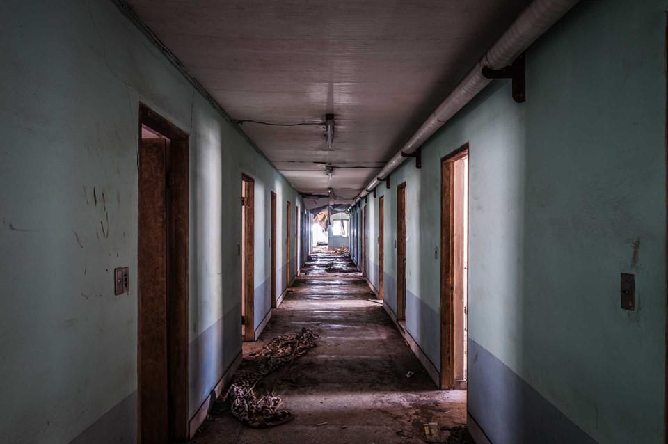 Tiến sâu vào bên trong, du khách sẽ bắt gặp dãy hành lang tối om, nhuốm màu u ám. Các phòng bệnh ngổn ngang đồ vật cũ. Ảnh: Shutterstock.