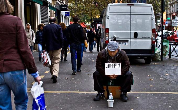 """Người đàn ông cầm tấm biển với dòng chữ """"Tôi đói""""."""