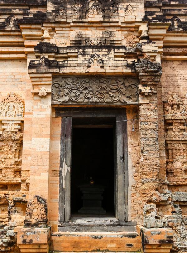 Cửa chính được xây nhô hẳn ra ngoài, rộng 1 m, cao 2 m. Trên cửa chính là một phiến đá lớn, hình chữ nhật, chạm nổi hình hoa cúc cách điệu. Ba mặt Tây - Nam - Bắc đều có cửa giả được đắp nổi các hoa văn, trang trí tinh xảo.