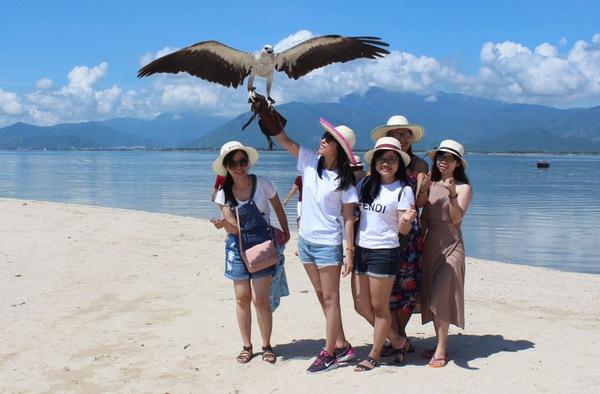 Nhóm du khách chụp hình với những chú chim được các bạn trẻ ở Khánh Hòa thuần nuôi, đưa ra Điệp Sơn cho khách thuê chụp hình.
