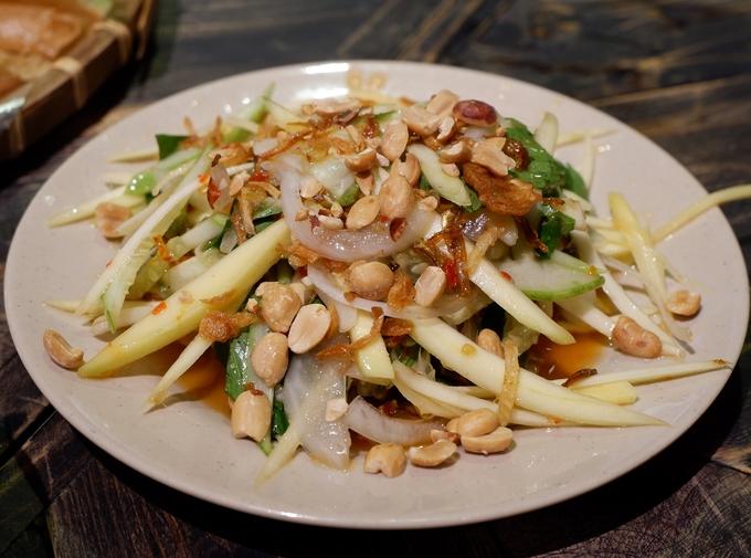Gỏi đu đủ xoài cá với cơm khô là gợi ý khai vị không tồi dành cho bạn. Cá cơm mặn, kèm thêm đậu phộng rang bùi và xoài chua ngọt kích thích vị giác.
