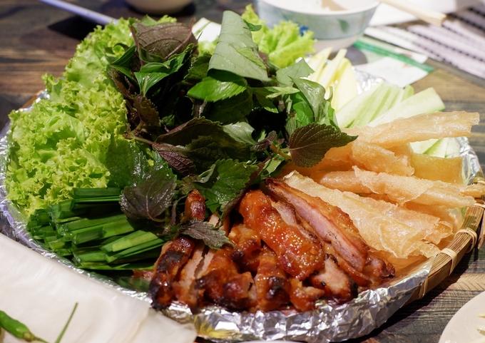Hay nem nướng Nha Trang cuốn với rau sống, bánh tráng chiên giòn chấm nước sốt chuẩn vị, ngon lành.