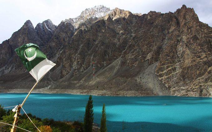 Hồ Attabad với màu nước xanh huyền diệu, xa xa là ngọn núi sừng sững, phấp phới trong gió lá quốc kỳ Pakistan.