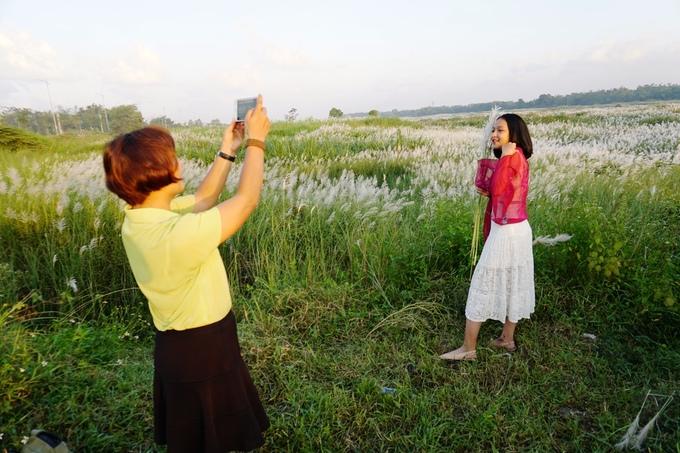"""Thân cỏ lau cao quá thân người nên không dễ để có được bức ảnh mà cả hoa và người đều đẹp. """"Tìm rất lâu tôi mới ra chỗ cao chụp được toàn cảnh cánh đồng phía sau"""", chị Huyền hứng khởi khi tìm được vị trí như ý."""