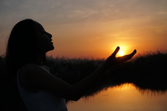 Cô gái chụp kiểu ảnh tay cầm ông mặt trời trên đồng cỏ lau lúc 18h.