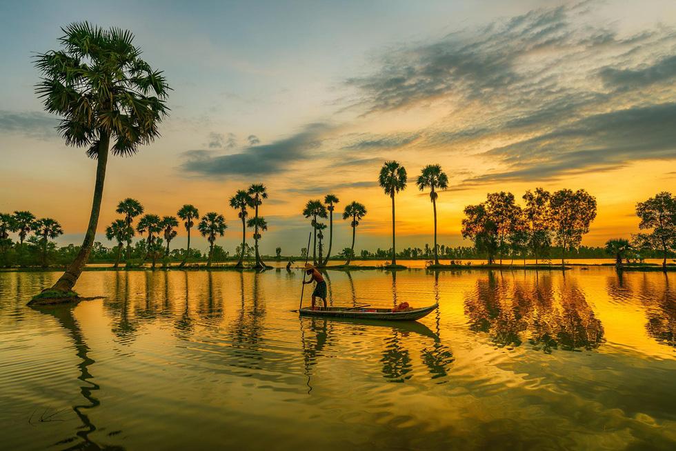 Một ngư dân đang chèo thuyền bắt cá tại cánh đồng ngập nước Tịnh Biên - Ảnh: MINH TRUNG