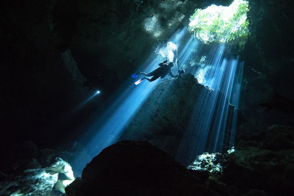 Một thợ lặn bơi dưới hang ngầm đang hướng về phía ánh nắng rọi xuyên qua bề mặt nước của hố sụt tự nhiên Taj Maha tại bang Quintana Roo - Ảnh: Donald Miralle/Getty/Lumix