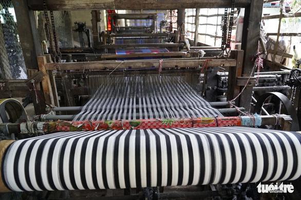 Máy dệt đáp ứng nhu cầu sản xuất số lượng lớn của làng nghề - Ảnh: NGỌC TÀI