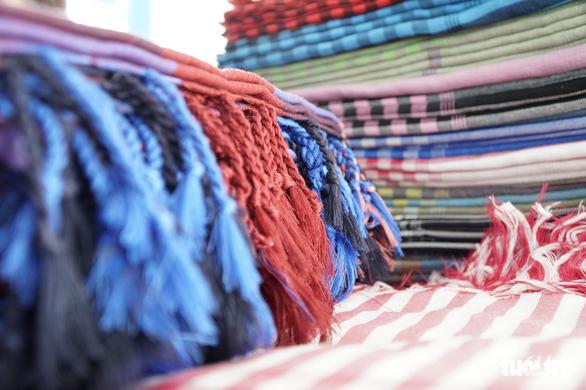 Cũng là những chiếc khăn rằn ngày nào, nay được tết chỉ ở đầu và cuối khăn, phù hợp làm khăn choàng cổ - Ảnh: NGỌC TÀI