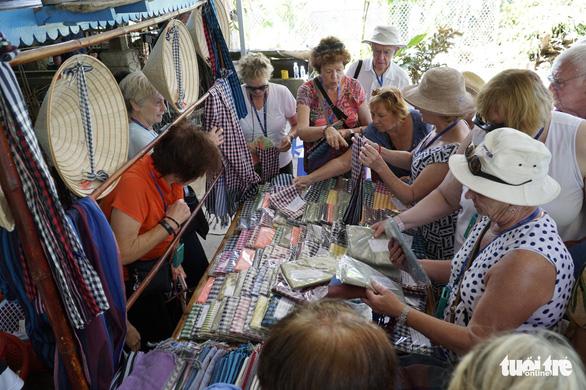 Ngày càng nhiều đoàn khách du lịch đến làng nghề dệt choàng Long Khánh tham quan, mua sản phẩm - Ảnh: NGỌC TÀI