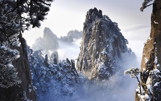 """Đỉnh Quang Minh: Đây là một trong 3 đỉnh cao nhất của dãy núi Hoàng Sơn, nằm ở phía nam tỉnh An Huy, miền Đông Trung Quốc. Khung cảnh ở đây hoang sơ, ấn tượng, với vô vàn loài kỳ hoa dị thảo, xen giữa núi đá trùng điệp.  Trong tiểu thuyết nổi tiếng """"Ỷ Thiên Đồ Long ký"""", Kim Dung chọn đây là đại bản doanh của Minh giáo. Đỉnh Quang Minh cũng là nơi diễn ra đại hội võ lâm, khi đó Trương Vô Kỵ đã một mình giải cứu Minh giáo. Ảnh: Hdwallpapersimages."""