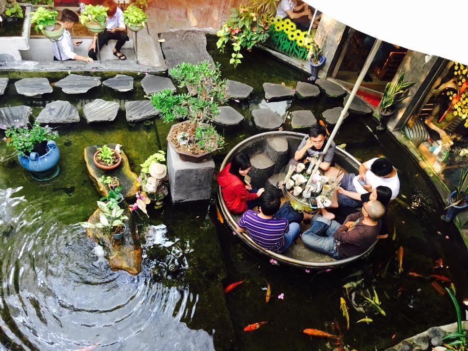 """Oasis Coffee  Không gian ngoài trời có lẽ là khu hút khách nhất của quán cà phê trên đường Lê Lợi, quận Gò Vấp. Cây cối được bố trí khắp nơi tạo cảm giác thoải mái, gần gũi thiên nhiên.  Phần không gian này còn được thiết kế thêm bàn ngồi dưới lòng hồ cá. Khách ngồi uống cà phê sẽ có cảm giác như đang """"bơi cùng bầy cá"""". Ảnh: Đỗ Hoàn Tuấn."""