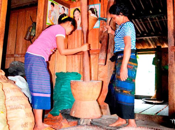 Sáng sớm, những phụ nữ ở bản Tà Vờng dậy từ rất sớm giã gạo nếp, sắn, ngô thành món cơm Pồi - Ảnh: HOÀNG BÙI