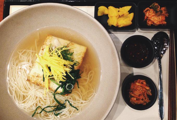 """Janchi-guksu (Mì yến tiệc)  Janchi-guksu có nghĩa là mì yến tiệc, bởi trong văn hóa ẩm thực Hàn Quốc, mì tượng trưng cho cuộc sống trường thọ và hạnh phúc nên thường xuất hiện trong các tiệc mừng năm mới, sinh nhật, mừng thọ, đám cưới.  Nhiều người gọi vui món này là """"mì không người lái"""" vì thành phần ít ỏi trong tô mì, chỉ gồm trứng, bí ngòi và đậu hũ. Hương vị của mì thanh tao, thích hợp để ăn nhẹ. Janchi-guksu thường được bán trong các nhà hàng và các quán ăn chuyên mì với giá không hề đắt."""