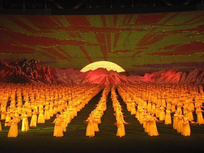 Hàng chục nghìn người trên khán đài sẽ phối hợp nhịp nhàng giơ cao các bảng màu để tạo thành bức tranh ghép khổng lồ, làm nền cho những vận động viên hoặc nghệ sĩ múa biểu diễn. Ảnh: Chris Price/Flickr.