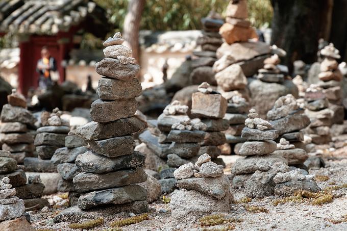 Phía sau chùa có một khuôn viên rộng là nơi nhiều người xếp đá chồng lên nhau như cách công trình được xây dựng. Người ta tin rằng mong ước của mình sẽ thành sự thật nếu như những cột đá này cao và vững chắc.
