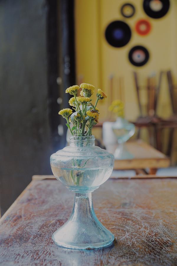Anh Hữu tận dụng những chiếc đèn dầu kiểu xưa để làm bình hoa. Đa phần vật dụng trong quán được chủ quán cất công đi đến nhiều nơi để sưu tầm. Nhờ cách sắp đặt khéo léo mà những trang trí này tạo mối liên kết hài hoà.
