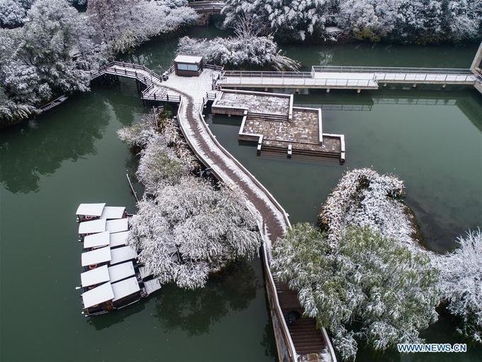 """Tuyết đầu mùa mới chỉ đủ phủ một lớp """"áo trắng"""" lên vạn vật cây cỏ, những chiếc thuyền nan nhưng chưa đủ để khiến dòng kênh đóng băng lạnh lẽo. Mặt nước xanh thẫm đối lập với khung cảnh tuyết trắng xoá."""