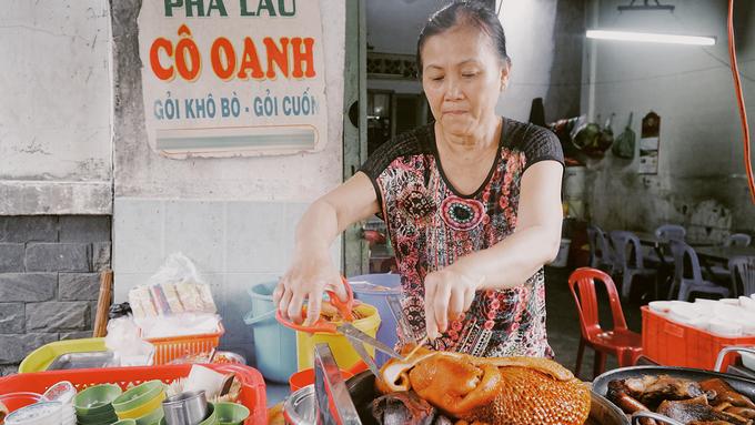 """Quán phá lấu Cô Oanh nằm trong một con hẻm nhỏ trên đường Xóm Chiếu - """"thiên đường ăn vặt"""" nổi tiếng ở Sài Gòn. Theo bà chủ, quán đã tồn tại được hơn 20 năm, """"khi món phá lấu chưa được nhiều người bán phổ biến và thực khách ưa thích như bây giờ"""", bà Oanh nói."""