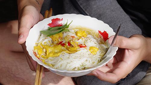 Bún cá  Bún cá nổi tiếng ở An Giang không do người Việt sáng tạo mà du nhập từ Campuchia. Sự thành công của món này nằm ở vị nước lèo được nêm nếm từ mắm cá linh, mắm ruốc. Nhiều quán còn hầm thêm xương ống để nước ngọt hơn. Nước lèo có màu vàng nhạt do còn có thêm củ nghệ giã nát. Bắc trên bếp lửa riu, cá hoà cùng nước hầm xương tạo nên thứ nước hấp dẫn.  Trong tô bún có các loại rau ở dưới cùng như bông điên điển là đặc sản từ những cánh đồng miền Tây. Nhiều nơi còn cho thêm thịt heo quay để ăn cùng. Suất ăn có giá bình dân từ 15.000 đồng. Ảnh: Di Vỹ.