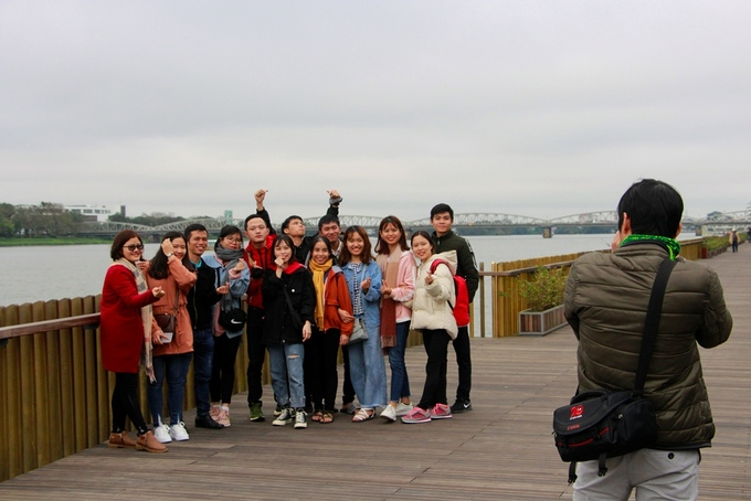 Nhóm bạn trẻ từ nơi khác đến Huế hào hứng chụp ảnh kỷ niệm ở cầu đi bộ lót sàn gỗ lim.