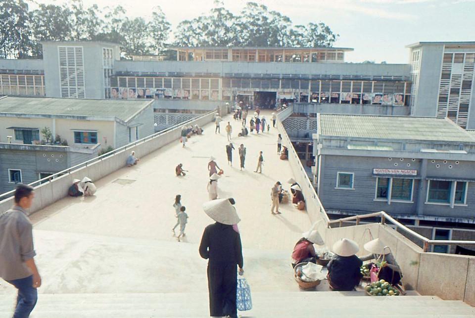 Chợ Đà Lạt xưa kia là nơi mua bán, giao thương sầm uất của thành phố. Ngày nay, chợ là điểm check-in đẹp tựa Hong Kong được giới trẻ yêu thích. Nơi này vào năm 1965-1966 vắng vẻ. Trong hình là cảnh những bà nội trợ xách làn ra chợ mua bán. Đà Lạt ngày ấy mộc mạc, đơn sơ, không có những hàng dài khách du lịch tấp nập đợi tới lượt chụp hình. Khuôn viên khu chợ theo đó cũng thoáng đãng, sạch sẽ. Ảnh: Anthony LaRusso.