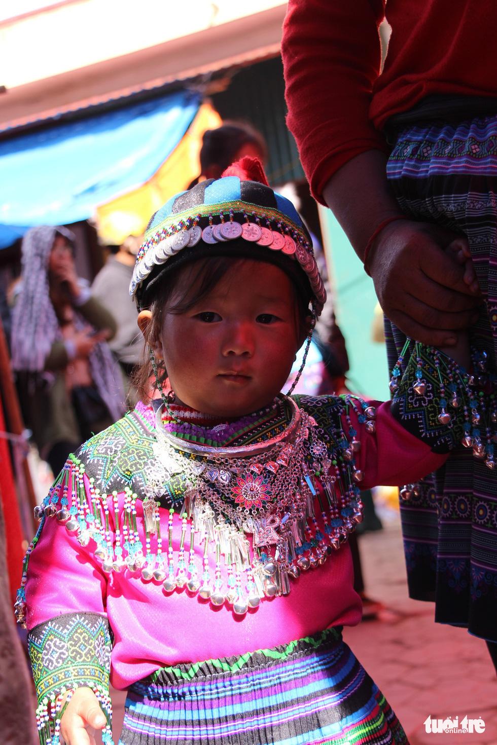Em bé người Mông theo mẹ xuống phiên chợ giáp tết được mẹ mặc cho bộ váy áo mới sặc sỡ