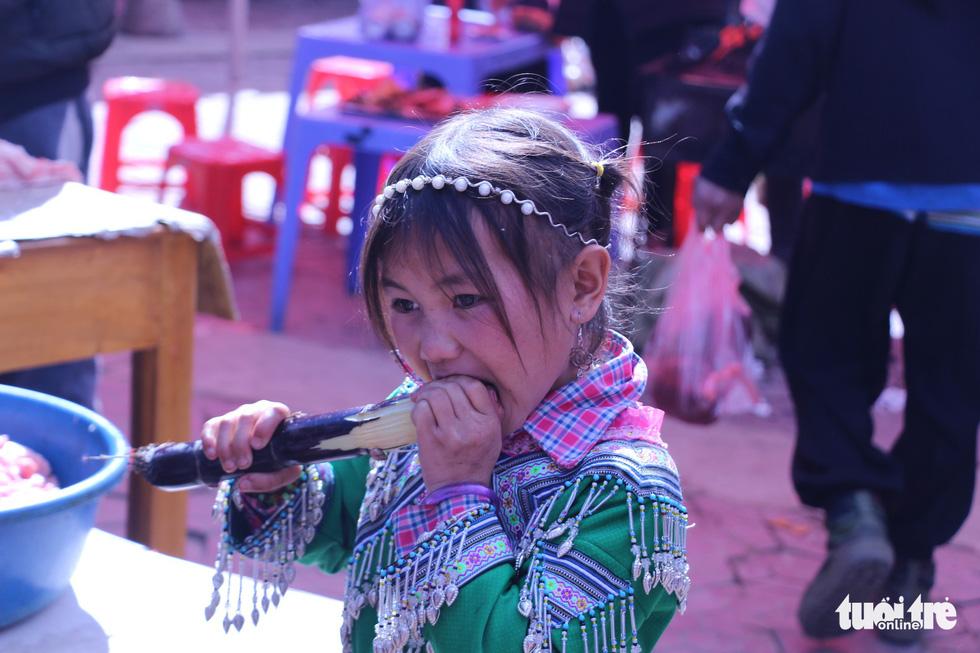 Trẻ con xuống chợ được mẹ cho tiền mua quà bánh ăn. Trong ảnh, một cô bé người Mông thưởng thức đọt mía mẹ mới mua cho. Đây là món ăn vặt ưa thích của đám trẻ con miền núi ở Y Tý