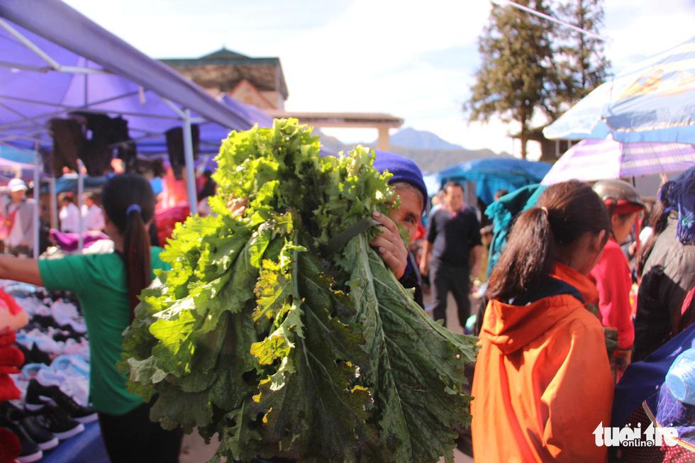 Một cụ bà khoe mớ cải xanh vừa mua tại chợ