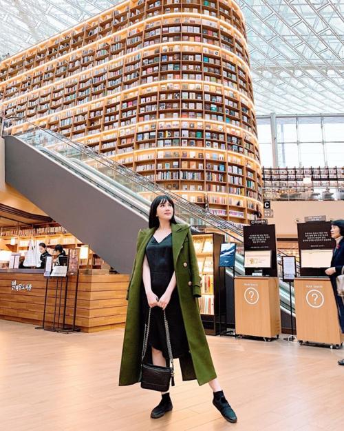"""Rất nhanh chóng sau đó, địa điểm này được bổ sung vào danh sách những điểm """"bắt buộc"""" phải ghé qua khi tới Seoul. Không chỉ dân du lịch bụi, các travel blogger tiếng tăm mà ngay cả các sao Việt cũng cập nhật ngay tức khắc điểm sống ảo cực chất này. Ca sĩ Bảo Thy là một trong những nghệ sĩ mê mẩn không gian rộng lớn có """"1-0-2"""" ở Starfield Library."""