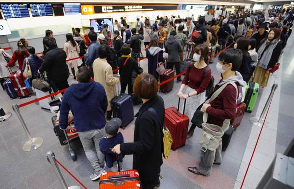 Các du khách xếp hàng chờ làm thủ tục tại sân bay Haneda, Nhật Bản - Ảnh: KYODO