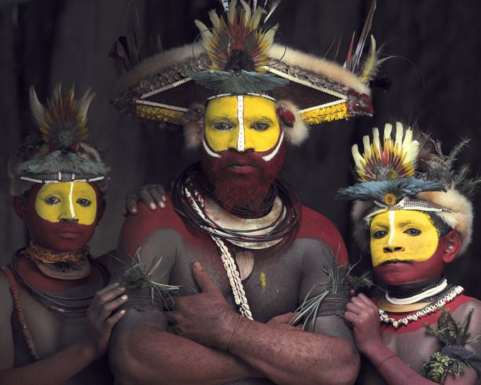 Trên ảnh là những người dân thuộc bộ tộc Huli, cộng đồng với dân số khoảng 250.000 người sống ở tỉnh Hela, Papua New Guinea. Họ nổi tiếng với phong tục đội tóc giả được trang trí từ lông vũ.  Ngoài những chiếc mũ công phu, người dân còn sơn mặt với các tông màu sáng như đỏ, vàng, trắng. Họ tin rằng đây là những màu sắc khiến họ trở nên dữ tợn và đe dọa được kẻ thù trong thời kỳ chiến tranh. Hiện nay, đàn ông Huli coi đây là trang phục truyền thống.