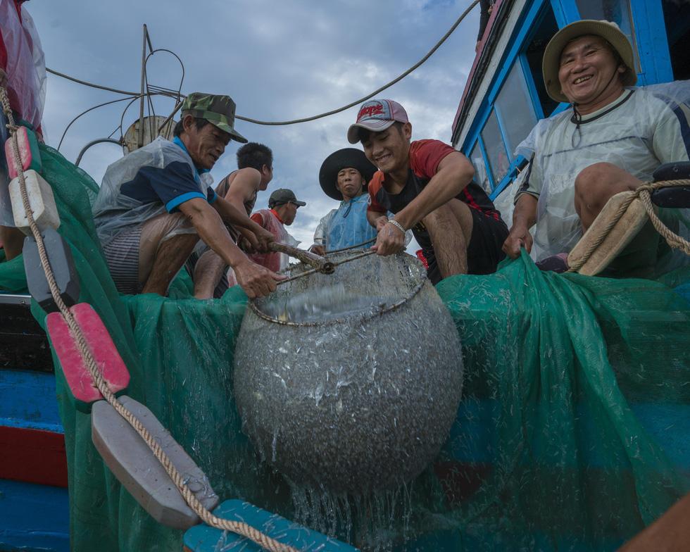 Nụ cười hạnh phúc được mùa cá cơm ngần của ngư dân - Ảnh: TRẦN BẢO HÒA