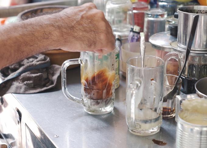 """Vì diện tích mặt bằng nhỏ bé nên trên bàn pha chế chỉ để một ấm đất đựng nước cà phê đen sánh cuối cùng sau vài lần đun chắt. Thao tác đun và hâm nóng được nhiều người gọi vui là """"cà phê kho""""."""