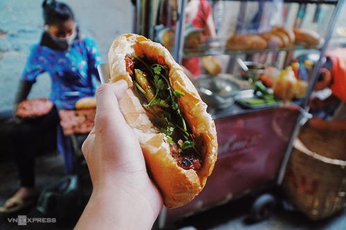 Bánh mì thịt nướng Nguyễn Trãi  Xe bánh mì nằm trong con hẻm nhỏ trên đường Nguyễn Trãi (quận 1) từng được tạp chí du lịch Mỹ Condé Nast Traveler nhắc tới trong danh sách 12 món ăn đường phố ngon nhất thế giới. Hàng chỉ bán duy nhất một loại nhân là thịt nướng, với loại sốt đặc biệt thay vì tương như ở nơi khác. Thịt nướng bán ở đây là viên thịt heo băm nhuyễn trộn gia vị kèm nước sốt theo công thức riêng của chủ rồi đem nướng trên vỉ bếp than ngay tại chỗ. Bếp nướng thịt tỏa mùi thơm quyến rũ cũng chính là đặc điểm để thực khách tìm ra vị trí xe bánh mì trong hẻm nhỏ.  Hàng này mở cửa từ 16h đến 21h và luôn đông nghẹt khách. Giá mỗi ổ là 20.000 đồng gồm 5 viên thịt, nước sốt và đồ chua.