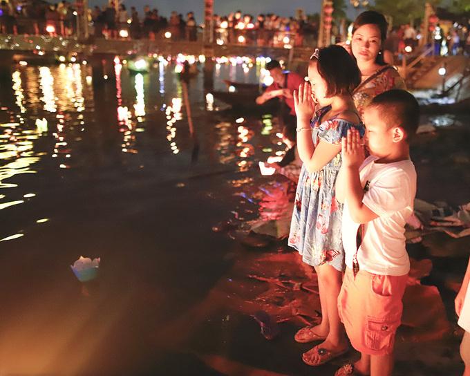 Du khách thả đèn để cầu bình an cho gia đình. Một chiếc hoa đăng làm bằng giấy, kèm đèn cầy bán giá cố định 10.000 đồng - Ảnh: Nguyễn Đông