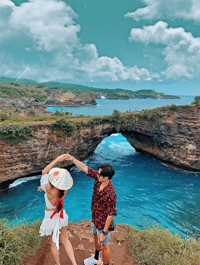 """Ngày thứ hai đặt chân tới Bali, Hoàng Kim và bạn đồng hành đã khám phá ngay sống lưng khủng long """"huyền thoại"""" trên Instagram và bãi biển Broken Beach. Đoạn đường tới đây mất 20 phút đi tàu, sau đó là đi xe qua ổ gà, ổ voi gập ghềnh nhưng khung cảnh ngoạn mục khiến cả hai rất mãn nguyện. Hai người thuê một hướng dẫn viên đưa đón, giá gồm cả vé tàu, ăn trưa, xe đi lại và chụp ảnh nhiệt tình cho khách."""