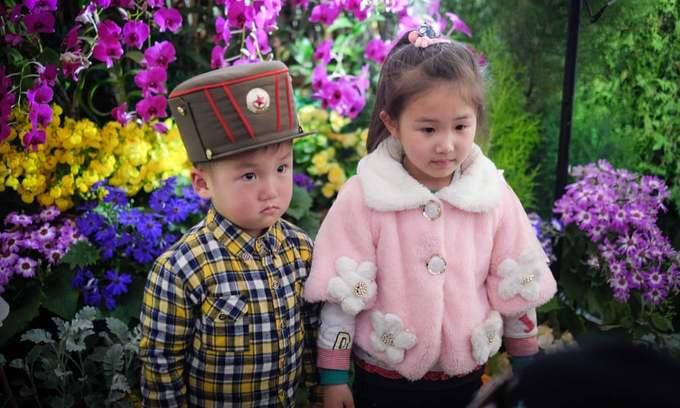 Hai em bé chụp ảnh trong triển lãm hoa kimilsungia và kimjongilia. Đây là hai loài được đặt theo tên của các nguyên lãnh đạo của Triều Tiên.