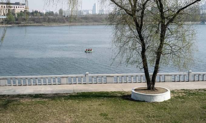 Ba người đàn ông chèo thuyền trên sông Đại Đồng (Taedong) chảy qua thủ đô Bình Nhưỡng. Dọc theo bờ sông là những công trình nổi bật khách tham quan thường ghé thăm như tháp Chủ Thể (Juche) và quảng trường Kim Nhật Thành.