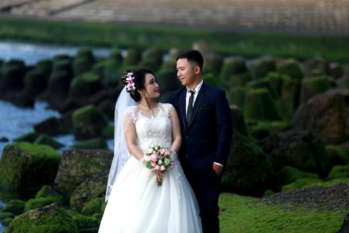 """Cô dâu tạo dáng bên những đám rêu ở biển để chụp ảnh. """"Từ Tết đến nay, tôi chụp gần 10 album ở đây rồi"""", anh Trần Duy Đạt (thợ chụp ảnh cưới) cho hay."""