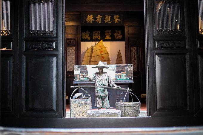 Bước qua cánh cửa gỗ lớn với bậc thềm cao, du khách sẽ thấy ngay những bức hoành phi sơn son thếp vàng được treo khắp nơi. Chính giữa là một khoảng sân nhỏ đặt bức tượng đá mô phỏng một lao động trong cộng đồng những người Hoa đầu tiên đến đây lập nghiệp.