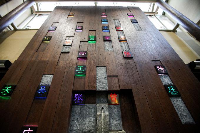 Bước qua khoảng sân trước, du khách sẽ thấy quầy lễ tân của khách sạn. Đối diện là một tấm bảng lớn được ghép từ nhiều thanh gỗ nhỏ có hơn 20 văn tự chữ Hán khác nhau.  Theo chủ khách sạn, đó là họ của những người đầu tiên đến đây lập nghiệp. Những họ này được dùng để đặt tên các phòng như một cách ghi nhớ công lao của những người khai phá, xây dựng nên nơi này.