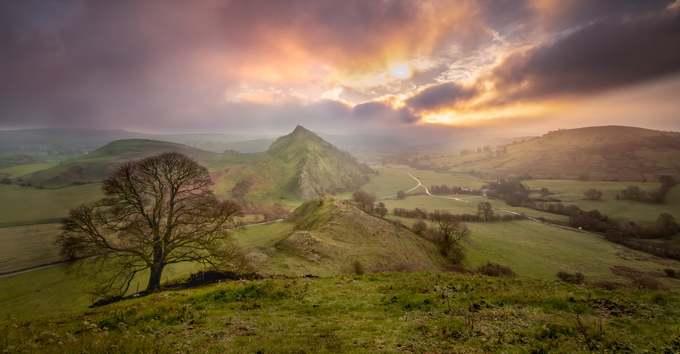 """Cuộc thi ảnh có chủ đề """"Khoảnh khắc thời gian"""" kỷ niệm 70 năm Nghị viện Anh thông qua đạo luật thành lập các công viên quốc gia. Cuộc thi thu hút trên 1.500 tác phẩm. Hiện có 15 công viên quốc gia được thành lập tại Vương quốc Anh, trong đó có 10 điểm ở Anh, 3 ở xứ Wales và 2 ở Scotland.  Giải nhất thuộc về tác giả Kieran Metcalfe chụp đồi Parkhouse thuộc công viên Peak District, nơi còn gọi là """"Sống lưng của Rồng"""". Peak District được thành lập vào tháng 4/1951. Ở khu vực trung tâm và phía nam của Peak District có các đỉnh đá vôi trắng bị xói mòn bởi băng tan thời kỳ Băng hà. Vườn quốc gia này có các loài động thực vật hoang dã phong phú. """"Tôi chụp bức ảnh vào một buổi sáng gió lộng tháng 11/2018, khi đứng trên đồi Chrome. Nhiều đám mây thấp bồng bềnh trôi và dường như che lấp ánh sáng đầu ngày. Tuy nhiên, ngay sau khi mặt trời nhô lên, các đám mây bắt đầu thưa dần và tôi bắt được khoảnh khắc vệt nắng rọi xuống"""", Metcalfe nói."""