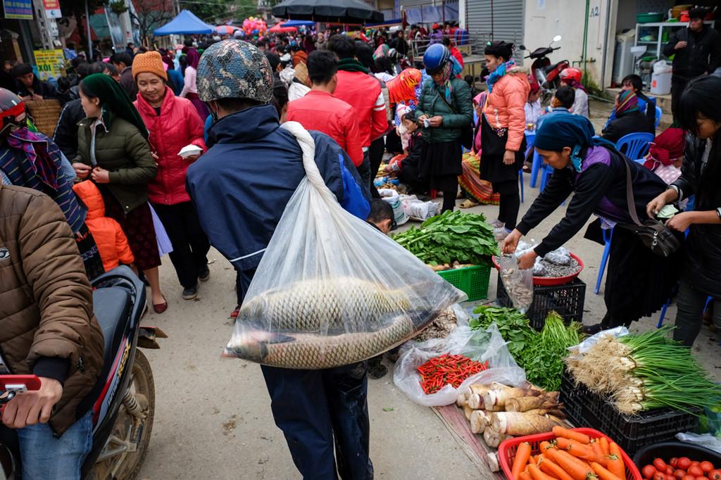 Một người đàn ông đang nhanh chóng di chuyển vào chợ để bán cá chép. Mặt hàng thực phẩm ở chợ phiên đa dạng với nhiều đặc sản của địa phương, bao gồm cả các loại rau củ đặc trưng.