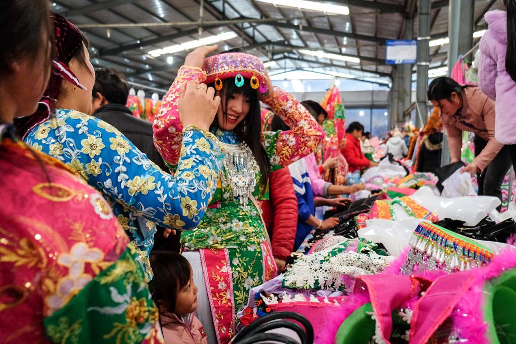 Một bạn gái người Mông đang thử khăn đội đầu, loại trang sức truyền thống của dân tộc thường được sử dụng trong các dịp lễ hội. Những quầy hàng bán quần áo tại đây luôn rất rực rỡ, thu hút cả người dân địa phương lẫn du khách ghé qua.