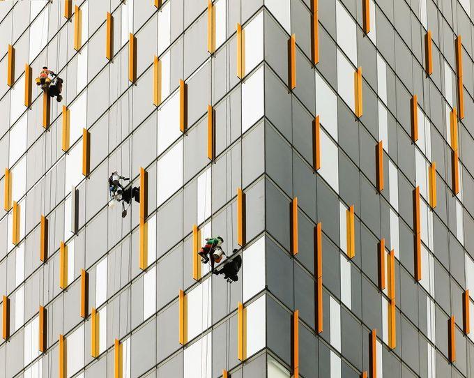 Hình ảnh những người thợ không sợ độ cao lau kính trên một tòa nhà cao tầng ở TP HCM đăng trên Daily Dozen ngày 1/12/2017.